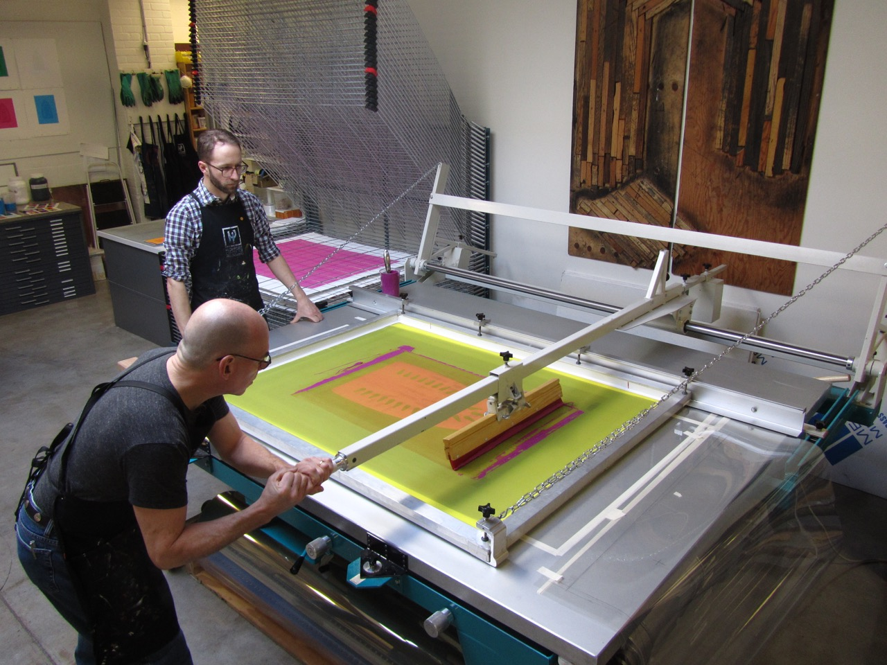 """'Master Printer Cole Rogers and Senior Printer Zac Adams-Bliss editioning Willie Cole's large-scale screenprints, 2012. Image Courtesy of Highpoint Editions"""""""